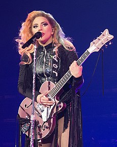 Lady Gaga standing behind a microphone stand with a pink guitar in her hands, wearing black leather fringe.