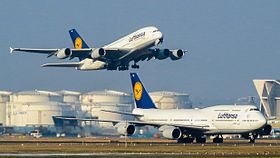 A Lufthansa Airbus A380 in the air about to land. In the foreground, a Lufthansa Boeing 747-8, is on the ground taxiing on a taxiway.