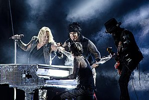 Mötley Crüe performing live in 2012, from left to right: Vince Neil, Nikki Sixx (background), Tommy Lee (foreground), Mick Mars