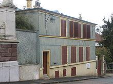 Photographie couleurs d'une maison à deux niveaux à volets rouges.
