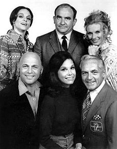 The original cast of The Mary Tyler Moore Show, 1970. Top: Valerie Harper (Rhoda), Ed Asner (Lou Grant), Cloris Leachman (Phyllis). Bottom: Gavin MacLeod (Murray), Moore, Ted Knight (Ted).