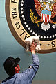 Master Sgt. Robert Klingelsmith, 89th Airlift Wing, polishes the presidential seal on Air Force One, A VC-135B Stratoliner aircraft F-3006-SPT-83-000038-XX-0301.jpg