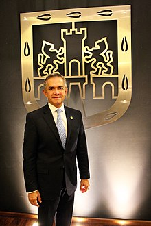Miguel Ángel Mancera stands in front of a golden shield depicting an old Mexico City's shield. He looks directly to the camera. He wears a black suit.