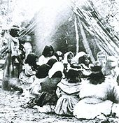 A group sits in front of a fire with a teepee made of large branches in the background.