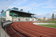 A brown running track lies within a small, open stadium below a blue sky.