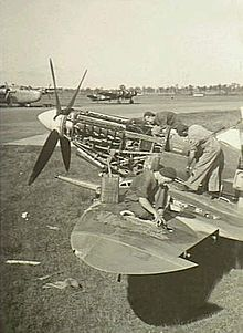 Three men servicing a single-engined military aircraft