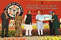 Narendra Modi presenting the award to Ms. Sonia Chauhan for suggesting the name 'Pradhan Mantri Jan Dhan Yojana (PMJDY)', in New Delhi. The Union Minister for Finance, Corporate Affairs and Defence, Shri Arun Jaitley.jpg