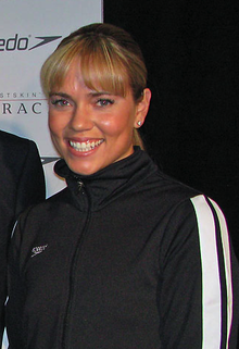 Woman with brown/blonde hair and a fringe, smiling. She is wearing a black Speedo tracksuit, and is standing in front of an advertising wall.