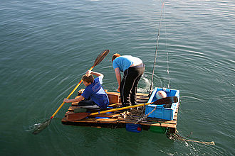 Traditional fishing boat - Boys fishing from a wooden crate raft