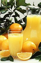 A jar of orange juice with oranges around it