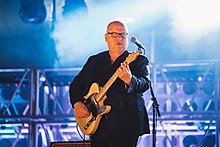 Black Francis playing guitar onstage, in front of a microphone