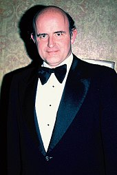 A man standing in a tuxedo, facing the camera with a slight smile