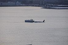 Photo montrant l'avion au milieu du fleuve Hudson, au centre de l'image, et l'arrivée d'un premier ferry à gauche de l'image, venant porter secours aux passagers, quelques minutes après l'amerrissage.