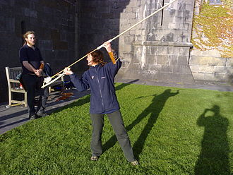 Spear-thrower - The thrower is checking to see that the dart has been correctly located on the spur of the spear-thrower; next she will turn her head in the other direction, aim and throw