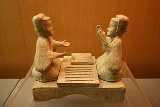Liubo - Eastern Han glazed pottery tomb figurines playing Liubo, with six sticks laid out to the side of the game board