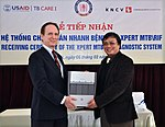 Prof. Dr. Dinh Ngoc Sy, manager of Vietnam's National TB Control Program (right), receives an Xpert Testing System from USAID Mission Director, Francis Donovan. (6828695265).jpg