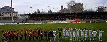 Photo de la présentation des équipes en début de match, les rouge et jaune à gauche contre les blancs à droite.
