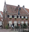 foto van Huis met lange zijde naar de Nieuweweg gewend. Kruisvensters, bovenverdieping lage vensters. Dakkapel met hijsbalk doorbreekt daklijst