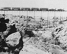 Un treno attraversa un ponte sulla linea transamericana nel 1860, trainato da due locomotive di tipo 4-4-0 American (rodiggio Whyte) e con al seguito alcune carrozze Pullman.