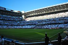The home fans are displaying the white of Real Madrid before El Clásico.  Spanish flags are also a common sight at Real Madrid games. 955bef7a377
