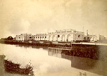 Photograph showing a canal running alongside a grand, white villa