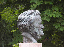 The grey scuplture of a head of a man in his sixties on a plinth with trees in the background. The front of his face is clean shaven but sideburns run under his chin.
