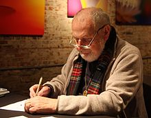 A gray-haired man seated at a table, wearing eyeglasses, a sweater, and a scarf draws with a pen in his right hand.