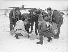 Black and white photograph of eight men in the snow looking at a map placed flat on the ground.