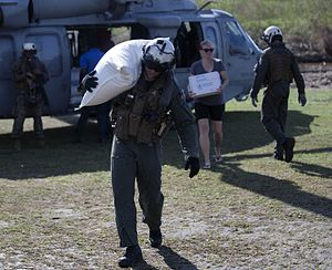 Effects of Hurricane Matthew in Haiti - An American soldier delivers aid to a damaged village