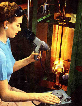 Czochralski process - Silicon crystal being grown by Czochralski process at Raytheon, 1956.  The induction heating coil is visible, and the end of the crystal just emerging from the melt.  The technician is measuring the temperature with an optical pyrometer.   One of the earliest Si plants, the crystals produced by this early apparatus were only one inch in diameter.