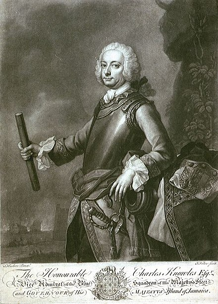 Commodore Charles Knowles in armour, one hand gestures to fortifications and a burning ship Sir Charles Knowles governor.jpg