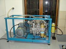 A small high-pressure compressor mounted on a steel frame with a three-phase electric motor for power. A flexible plastic air intake hose provides fresh air from outside of the building.