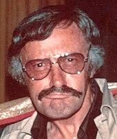 photo en couleur en gros plan d'un visage d'homme d'une cinquantaine d'années portant des lunettes et une moustache.