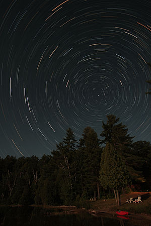 Celestial pole - Over the course of an evening in the Northern Hemisphere, circumpolar stars appear to circle around the north celestial pole. Polaris (within 1° of the pole) is the nearly stationary bright star just to the right of the center of this star trail photo.