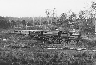 North Coast railway line, Queensland - The half past two passenger train from Cooroy crossing the bridge just beyond the Butter Factory, Eumundi, 1915