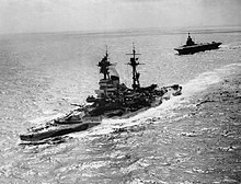 A large warship steaming through a calm sea with a large, flat-decked warship following behind