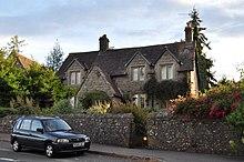 Une petite maison de village en pierre grise, envahie par la végétation et bordée d'un muret en pierre