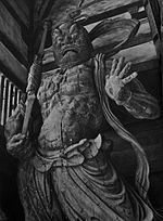 Agyō. Front view of a scary statue carrying a spear like object in his right hand and the palm of his left hand facing the viewer with fingers spread. Sculpted breastplate and necklace are visible.