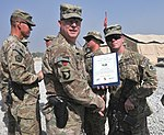 U.S. Army Brig. Gen. Duane Gamble, center, the deputy commanding general of the 1st Sustainment Command, awards a Combat Action Badge to Spc. Austin C. Fleischer, with the 864th Engineer Battalion, assigned to 131007-A-WQ129-009.jpg