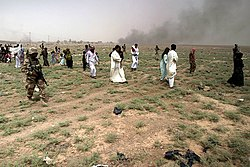 Civilians being escorted away from fighting in Al-Karābilah during the Iraq War, 2005