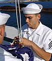 US Navy 040531-N-9643K-009 Yeoman Seaman Gabriel Gonzales assigned to the Los Angeles-class submarines USS Greeneville (SSN 772) prepare to bring the flag to half-mast.jpg