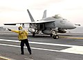 US Navy 040708-N-8213G-048 Aviation Boatswain's Mate Airman Vince Pascua, of San Diego, gives directions to a F-A-18E Hornet.jpg