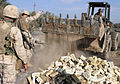 US Navy 041113-M-1250B-017 A U.S. Navy Seabee assigned to the 24th Marine Expeditionary Unit (MEU), drops dirt and bricks into an impact hole on a bridge in Lutafiyah, Iraq.jpg