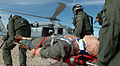 US Navy 051202-N-6901L-276 U.S. Navy air crewmen assigned to Helicopter Sea Combat Squadron Two One (HSC-21), carry a training mannequin simulating an injured soldier, to an MH-60S Seahawk helicopter.jpg