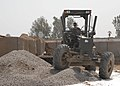 US Navy 070420-N-3560G-021 Equipment Operator 2nd Class Hayden Coleman assigned to Naval Mobile Construction Battalion (NMCB) 4 operates a grader, spreading gravel on a newly constructed parking lot.jpg