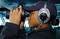 US Navy 070518-N-4420S-115 Operations Specialist Seaman Caitlyn Hagedorn looks through a pair of binoculars while standing lookout watch aboard nuclear-powered aircraft carrier USS Nimitz (CVN 68).jpg
