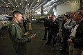 US Navy 070704-N-7883G-064 Lt. j.g. Andrew Babakan, assigned to the Diamondbacks of Strike Fighter Attack Squadron (VFA) 102, explains the various types of aircraft in the hangar bay to Australian visitors aboard USS Kitty Hawk.jpg