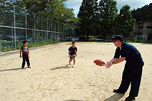 Catch (game) - A U.S. Navy sailor plays catch with some children in Japan.