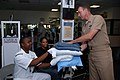 US Navy 071023-N-5086M-004 Senior Chief Hospital Corpsman Trevor Dallas-Orr hands blankets and pillows to Personnel Specialist 1st Class William Clincy and his wife for their stay at the temporary evacuation site on base.jpg