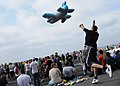 US Navy 080822-N-9898L-463 Yeoman 3rd Class Bryan Patino, from Imperial Beach, Calif., tosses an airplane-shaped pool toy into the audience during a break in a karaoke session during a steel beach picnic on the flight deck of t.jpg